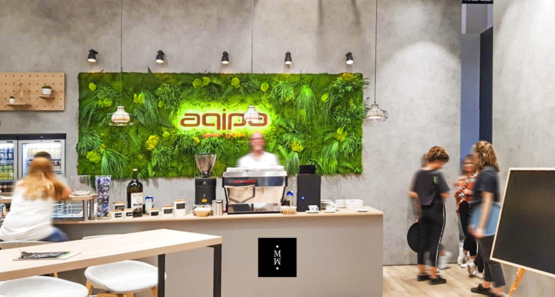 Dschungelmooswand hinter einer Bar mit Logo